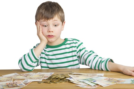 cash desk: Young boy is looking amazed at a lot of money