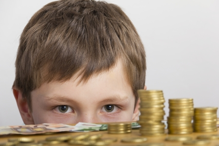 Boy looking at towers of money Stock Photo