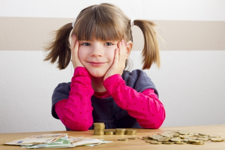 Happy girl sitting in front of a lot money Stock Photo