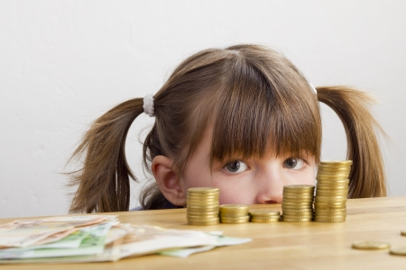 little table: Girl looking at towers of money Stock Photo