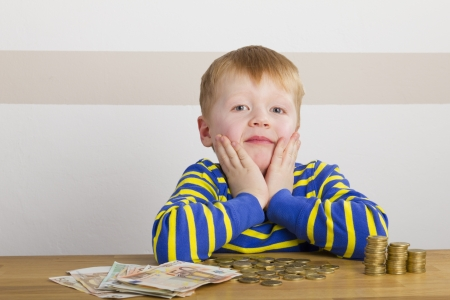 Boy sitting in front of a lot of money photo