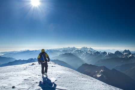 A man stands on top of Mount Elbrus