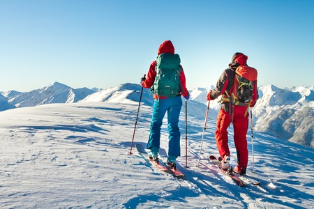 Man and woman ski tourer enjoying the view on a summit in the alps. Stockfoto