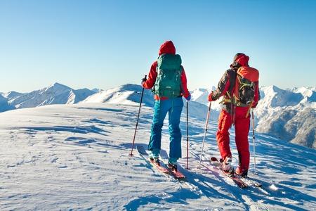 Mann und Frau Skitourengeher genießen die Aussicht auf einen Gipfel in den Alpen. Standard-Bild