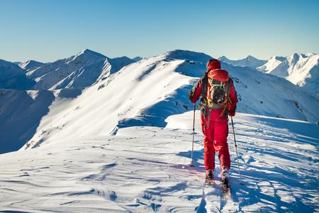 Männlicher Skitourengeher, der die Aussicht auf einen Gipfel in den Alpen genießt