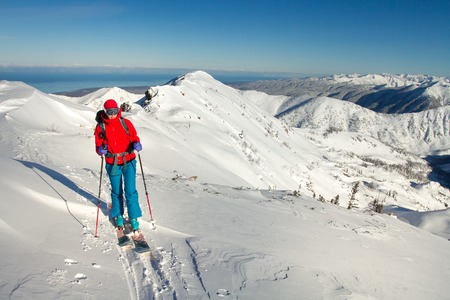Girl makes ski mountaineering alone toward the mountain pass in a nice track with sealskin Reklamní fotografie