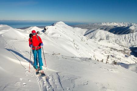 Meisje maakt ski-alpinisme alleen naar de bergpas in een mooie baan met zeehondenleer Stockfoto