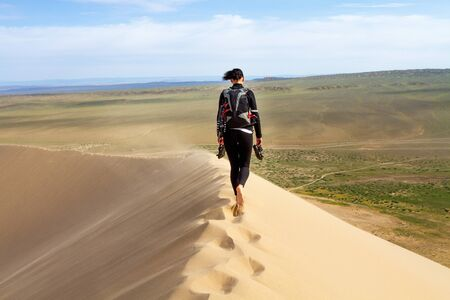 Woman walking in the mongolian desert sand dunes. Young woman walking golden sand on a bright summer day, Mongolia holliday vacation concept.