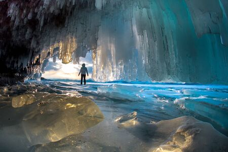 Surreal landscape with people exploring mysterious ice grotto cave. Outdoor adventure. Family exploring huge icy cave, dark majestic landscape. Magical silhouettes on background of illuminated ice Banco de Imagens