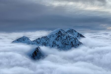 Snowy Alpen peaks above clouds. Sunset time.