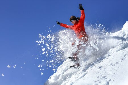 Happy young girl jumping to snowdrift. Sunny day. Imagens