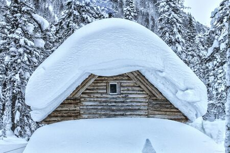 Beautiful winter mountain landscape with snowcapped wooden hut.