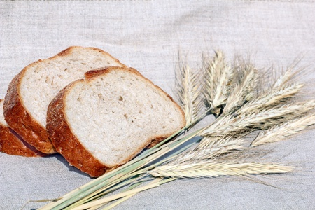 pieces of fresh soft bread with cereal ears on linen Stock Photo - 10032179