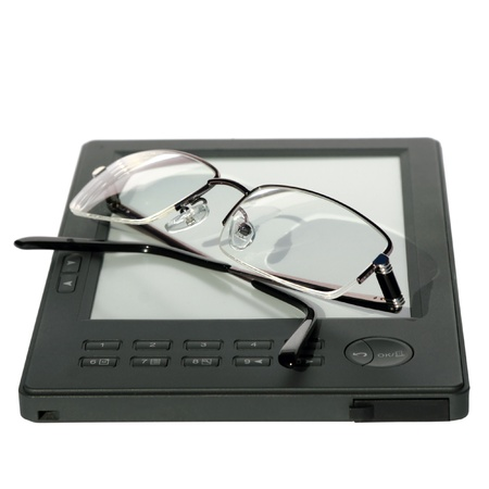 glasses lying on the e-book reader device, close up, isolated