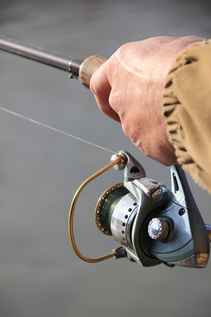 fishing pole: Fisherman with spinning on the river Stock Photo