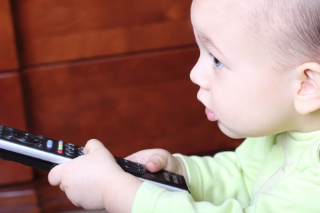 blue eyed: little child with a TV remote control close up