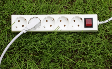 electric power receptacle and plug on the grass, energy concept