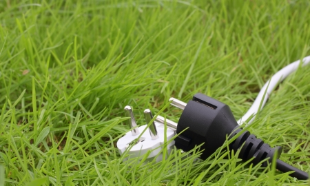 switchplug lying on the grass, energy concept photo