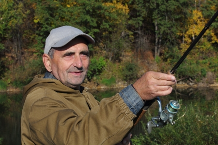 old fisherman with spinning on autumn river Stock Photo - 15385821