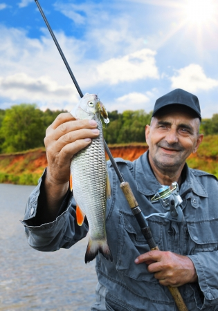 chub: chub in the hand of fisherman against the sky and the river