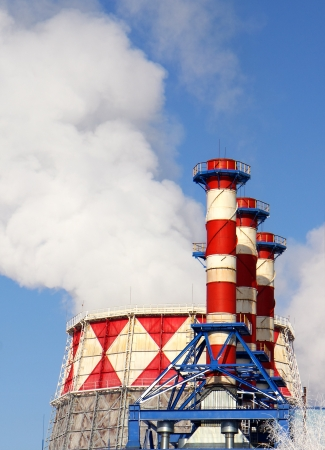 atmosphere construction: Smoking pipes of gas-turbine plant against blue sky