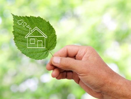 eficiencia energetica: Casa ecol�gica concepto, mano que sostiene icono de la casa ecol�gica en la naturaleza Foto de archivo