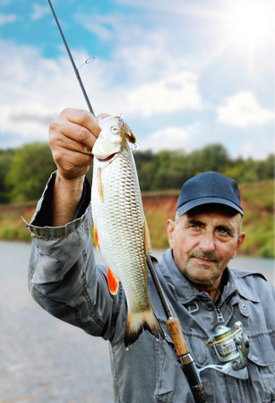 pisciculture: chub in the hand of fisherman against the sky and the river