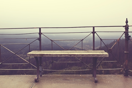 bench alone: bench on a hill with mountain scenery around Stock Photo