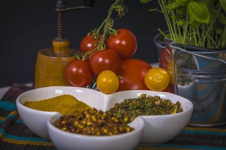 tomatoes, basil and spices on dark grunge backdrop Stock Photo