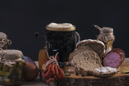 dark beer with dark bread, pickles and sausage