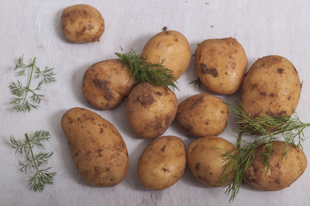 Fresh raw potatoes on a white wooden background. Top view Stock Photo