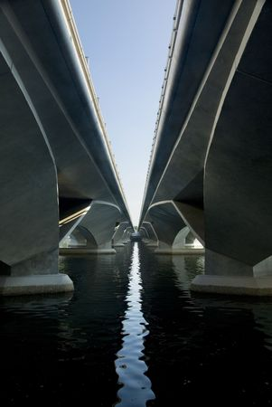 An ultra modern concrete freeway bridge spans a river.