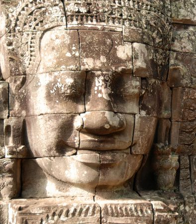 A large and peaceful face is carved into the mighty temple of Bayon, Cambodia. photo