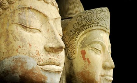 social history: Close up of two ancient stone Buddhas