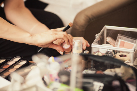 bridal salon: A set of brushes for make-up on the table and see the hands of make-up