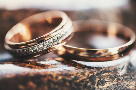 silver jewelry: Two gold wedding rings lie on a wooden surface