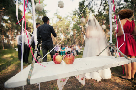 witnesses: Betrothal ceremony in the woods. In the foreground, two apples on a swing