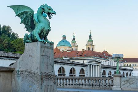 river: Green dragon on Dragon bridge in Ljubljana with market and church of Saint Nicholas