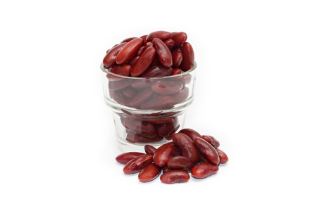 Red beans boiled in a glass on a white background Фото со стока
