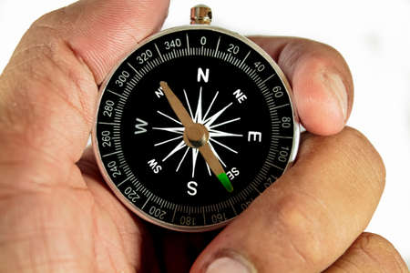 Hand Holding Compass on White photo