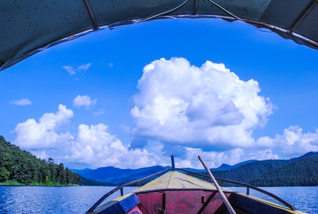 The Thai excursion boat floats to dam and fancy cloud Stock Photo
