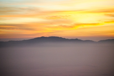 colorful summer morning with golden light and fog between hills Stock Photo
