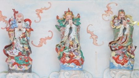 Statue of three Chinese god on top of a temple