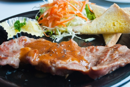 A grilled top sirloin steak of pork ,with bread,salad and fresh mashed potatoes Stock Photo