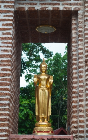Golden buddha standing in a brick wall frame  at the entrance to the temple gate  photo