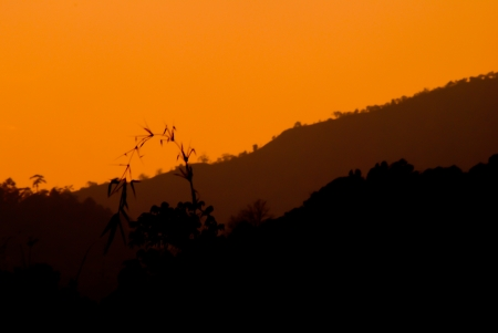 Sunset silhouette of the mountains and forests. Wiang Pa Pao district, Chiang Rai, Thailand. photo