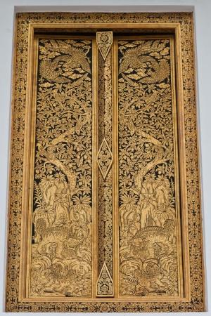 Golden Thai design craft on wooden door in Thai temple. Stock Photo - 14842159
