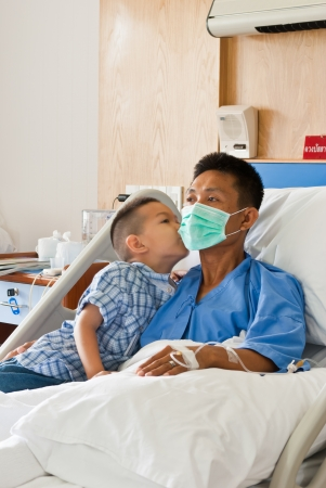 a patient and son with saline intravenous  iv  on hospital bed Stock Photo
