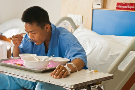 Patient  with saline intravenous  iv  on hospital bed eating his lunch on a tray