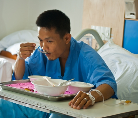 Patient  with saline intravenous  iv  on hospital bed eating his lunch on a tray Stock Photo - 14798423